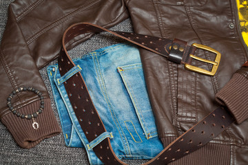 Brown leather jacket, jeans with a belt, shirt and bracelet