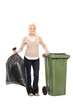 Woman holding trash bag next to a garbage bin