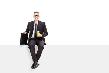 Businessman holding a cup of coffee seated on panel