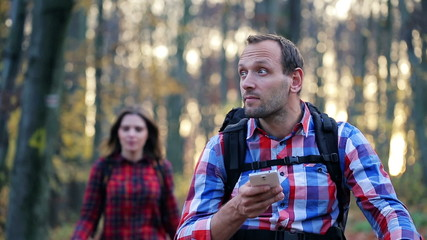 Young man with smartphone looking for direction in forest
