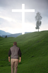 Man walking tot he cross in green field
