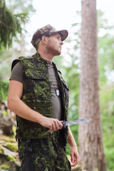 young soldier or hunter with knife in forest