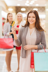 women with shopping bags and credit card in mall