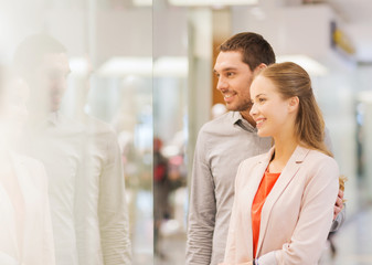 happy couple looking to shop window in mall
