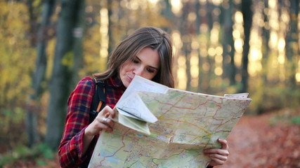 Young, pretty woman with map looking for direction in forest
