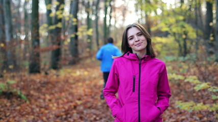 Portrait of smiling female jogger in autumn forest