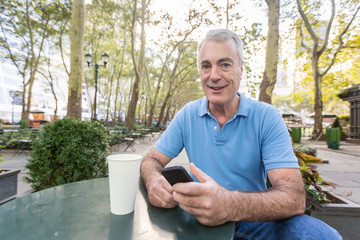 American Senior Man with Mobile Phone at Park