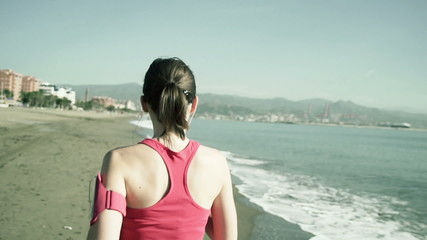 Young woman jogging along the beach shot at 120fps