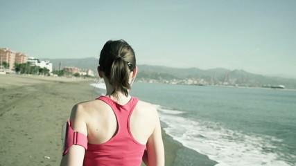 Young woman jogging along the beach shot at 120fps