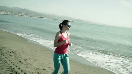 Young, pretty woman jogging along the city beach