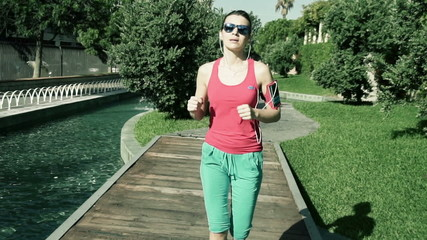 Young, pretty woman jogging in park, shot at 120 fps