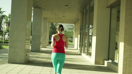 Sporty woman jogging in the city during sunny day, slow motion
