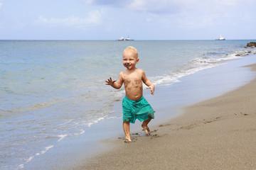 One year baby boy walking on the beach