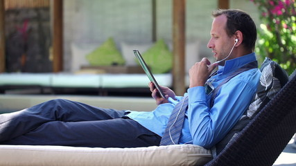 Businessman with tablet chatting on cellphone, lying on sunbed