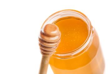 opened honey jar on white background near wooden honey dipper