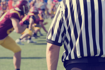 American football referee and de-focused players.