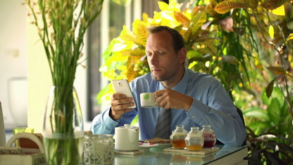 Businessman with smartphone by the table in the morning