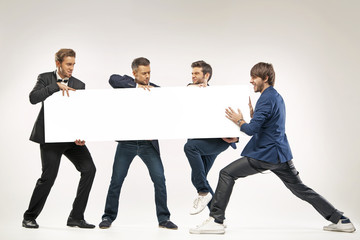 Four guys pushing the billboard