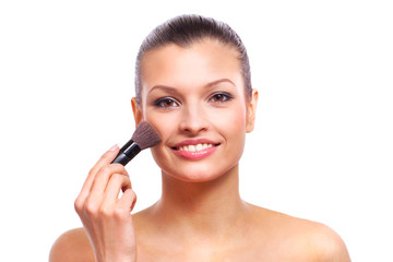 Beautiful young woman applying cosmetic paint brush