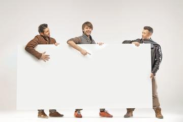 Young joyful guys holding white board