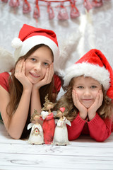 Two glad sisters with santa caps