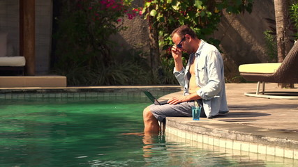 Young man sitting with laptop in swimming pool