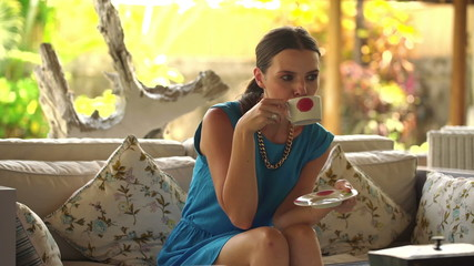 Young, pretty woman drinking tea on sofa at home