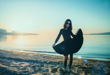 Beautiful woman in black dress on beach