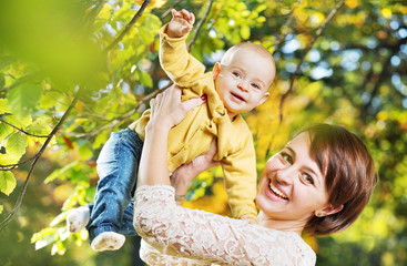 Charming wife carrying little child