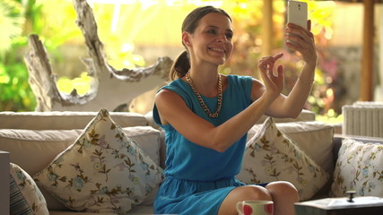 Young woman taking selfie with her cellphone on sofa  at home