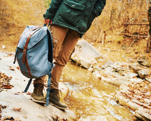 Hiker with backpack standing near a creek
