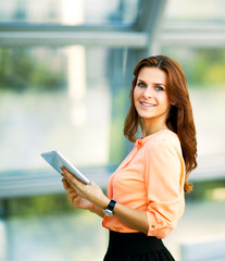 Young smiling business woman holding digital tablet