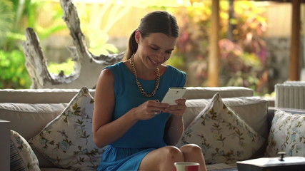 Young, happy woman texting, using smartphone at home