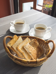 Toasts in basket with coffee on table.Breakfast set