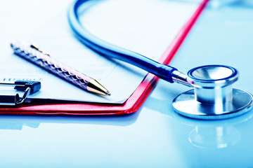 medical history with stethoscope and pen