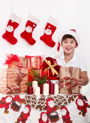 Boy in red hat with Christmas gifts