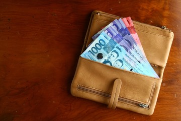Cash money in a leather wallet