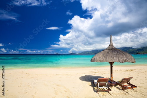 Perfect tropical beach with chairs and umbrella