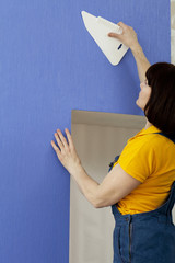 Woman smoothing wallpaper