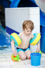 Little cute child playing and having fun in swimming pool