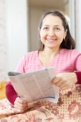 Smiling mature woman reads newspaper