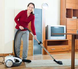 Happy mature woman cleaning with vacuum cleaner