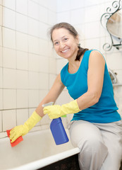 Smiling mature woman cleans bathroom