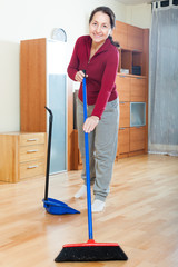 mature woman sweeping the floor