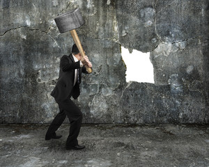 businessman hold sledgehammer cracking big white hole on concret