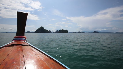 longtail Boat sailing to the islands in azure water sea
