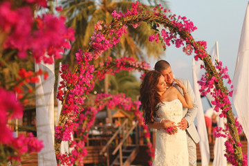 Bride and groom embracing near arch of flowers in Maldives