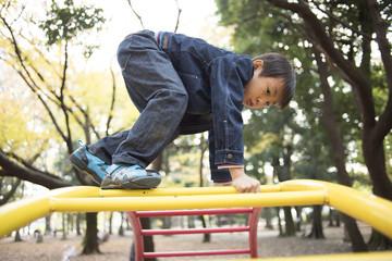 Boy climbing on playground equipment