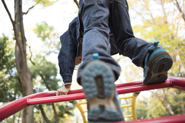 From behind of children climbing on playground equipment