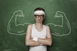 Funny sport nerd with fake muscle drawn on the chalkboard - 73769230